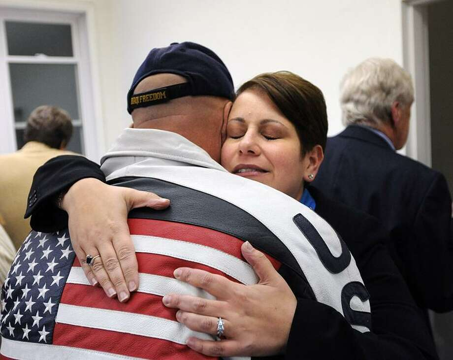 East Haven-- East Haven Mayor April Capone gets a hug from supporter, Bob Nappe, after Capone lost the election to Joe Maturo by 30 votes. Nappe is an East Haven police officer.  Peter Casolino/New Haven Register11/08/11