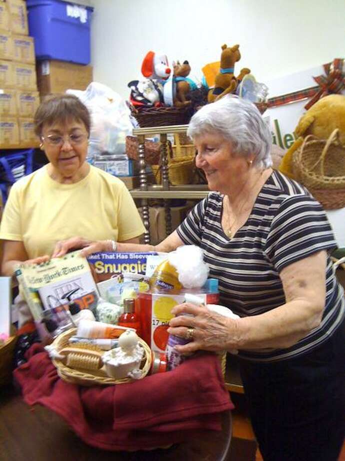 Ann DeMatteo/Register photo: Annette LaVelle, co-president of the Hamden Woman's Club, left, and Mary Jane Landino, the club's home co-chair, work on auction baskets at Sacred Heart Manor in Hamden for the Clelian Center's 11th annual Hawaiian Sizzle and Surf dinner and auction Friday.