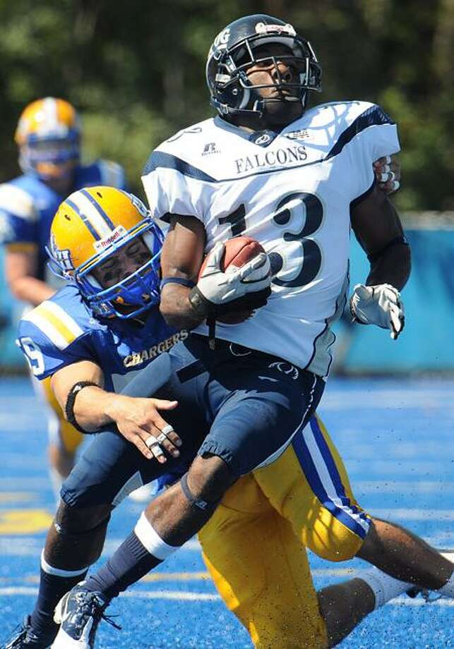 West Haven-- UNH's Cody Wallace puts the hit on Saint Augustine's Jamian Smith during the second quarter.  Peter Casolino/New Haven Register9/10/11