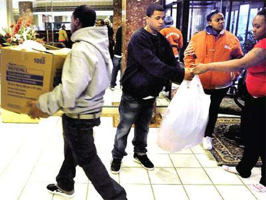 Brentell Roberson, left, his brother, Brandon, both of New Haven, and their cousin, Terri Payne of West Haven, far right, accept clothing donations fromPayne's friend, Wannona Carney of West Haven, second from right. The Robersons are homeless following the Wednesday fatal fire at 48-50 Wolcott St. in Fair Haven. (Mara Lavitt/Register)