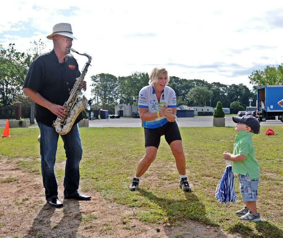 "Darriell Rolka dances with her grandson Wyatt Verrillo, 2, as Jim Pino of the band ""Freeplay"" plays saxophone at the Yale Bowl in New Haven. Rolka had just finished a 25-mile ride in the inaugural ""Closer to Free"" bike ride. The ride benefits cancer research and clinical programs at the Smilow Cancer Hospital at Yale. Rolka is from Guilford, and Verrillo is from Branford.  Peter Casolino/Register  9/10/11"