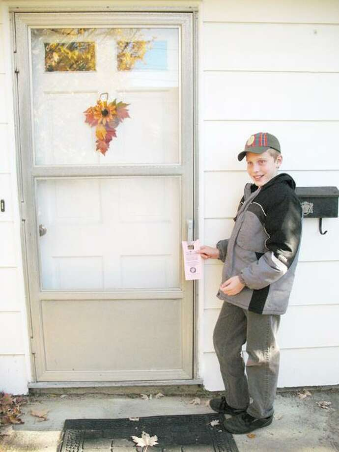 SUBMITTED PHOTO Scout Harry Jones hangs up reminder tags for the Scouting for Food campaign. Boy Scouts and Cub Scouts delivered them on Saturday, Nov. 5.