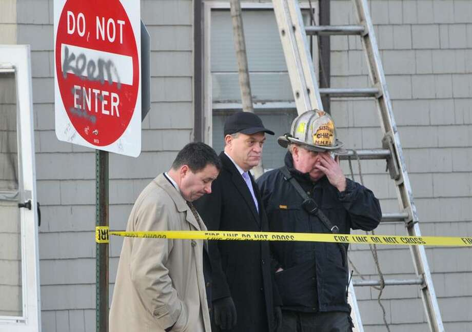 New Haven Fire Chief Michael Grant, right, shows New Haven John DeStefano Jr. , center, around the house that was engulfed in flames earlier Wednesday morning. (Brad Horrigan/New Haven Register)