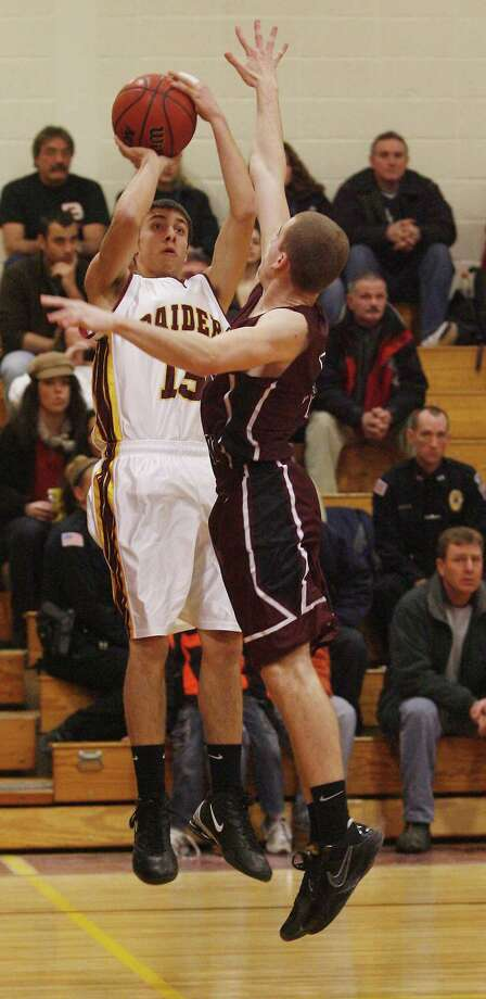 Dispatch Staff Photo by JOHN HAEGER Canastota's Jeff Merrell (15) goes up for three as S-E's Randall Briggs (4) defends in the first half of the game   on Thursday, Jan. 13, 2011 in Canastota.
