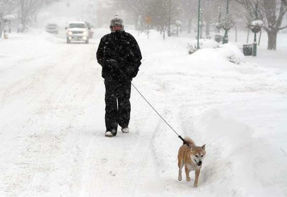 A man who choose not to give his name, walks his dog on Main Street. in Branford Wednesday morning during the snowstorm 1/12/11.Photo by Peter Hvizdak / New Haven Register    January 12 2011      ph2636   Connecticut