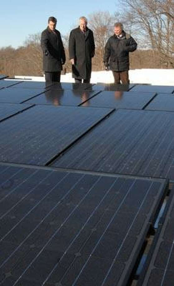 From left, Joseph A. Foran High School Principal John Barile, Deputy Superintendent of Operations Philip G. Russell and HUD Block Grant Coordinator Thomas Ivers look at solar panels being installed on the school's roof. (Peter Hvizdak/Register)