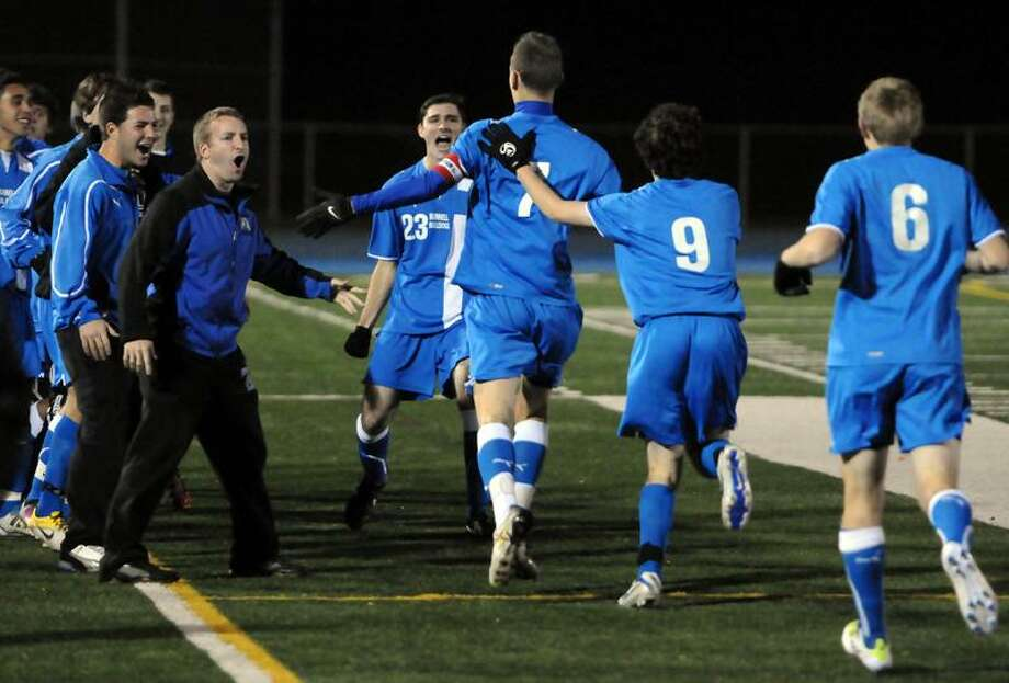 Pomperaug at Bunnell, SWC Soccer Championship boys, first half: Justin Lewis is congratulated by his teammates after scoring Bunnell's first goal. Photo by Mara Lavitt/New Haven Register11/7/11