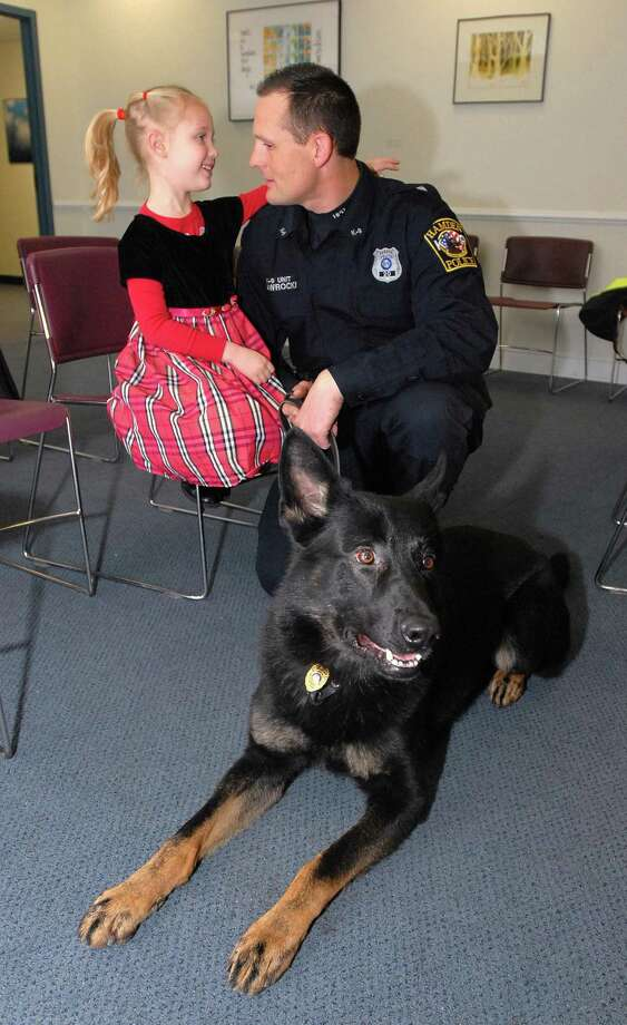"Hamden Police Officer Mike Nawrocki shares a moment with his daughter, Julia, moments after his dog ""Hank"" was sworn in as the newest member of the department at Town Hall in January 2010. File photo by Peter Casolino/New Haven Register"
