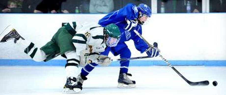 C.J. Carignan (left) of Hamden defends against Dave Landino (right) of West Haven in the first period of their game on 3/9/2011.Photo by Arnold Gold/New Haven Register     AG0405A