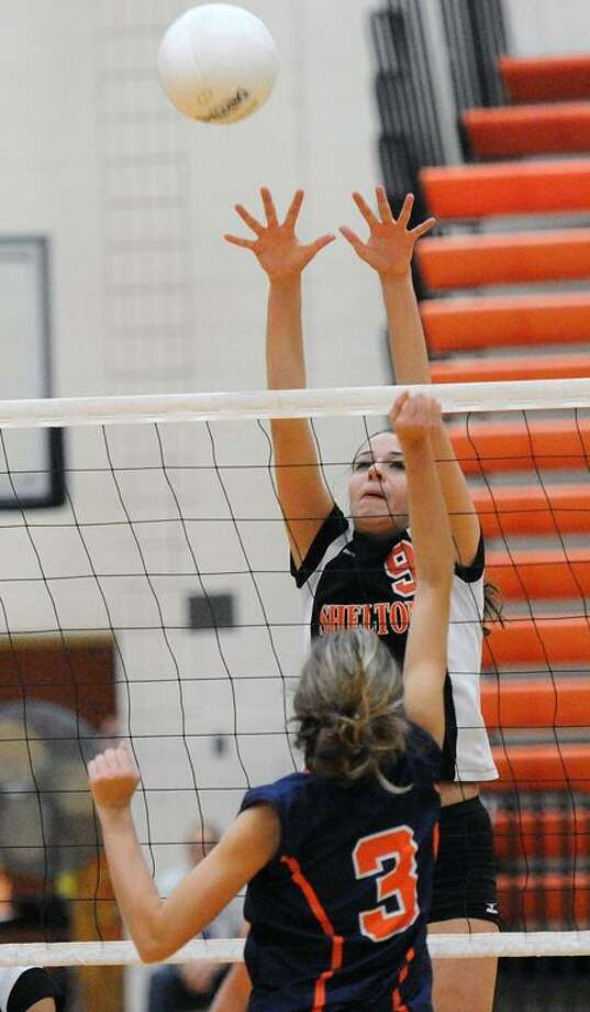 Shelton's Katie DiRenzo makes the block against Lyman Hall's Bre Tolla during the first set in a recent match. Peter Casolino/New Haven Register.