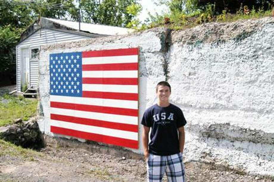 Dispatch Staff Photo by MATT POWERSStockbridge Valley Central School Valedictorian Charlie Wilson Jr. stands next to the rearranged American flag mural at the Munnsville American Legion Post 54.