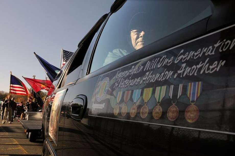 Ed Berberich, 84, of Milford and a U.S. Navy SeaBee who served from 1945 to 1947, rides in an SUV  with members of the  Vietnam Veterans of America Sunday, Nov. 6, during the  Milford Veterans Day Parade. Peter Hvizdak/Register / PETER HVIZDAK