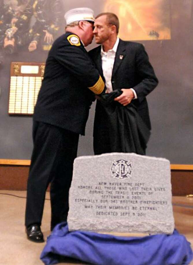 New Haven Fire Chief Michael E. Grant, left, hugs his friend, retired New York City Firefighter Tim Brown of Rescue Co. 3, after the unveiling Friday of a Memorial Stone honoring all the people who died in the World Trade Center attacks, including the firefighters who lost their lives. A memorial service was held Friday at the New Haven Regional Fire Training Academy to commemorate the 10th anniversary of the attacks. Brown was a first responder to the World Trade Center. Peter Hvizdak/Register    September 9, 2011       ph2360                Connecticut