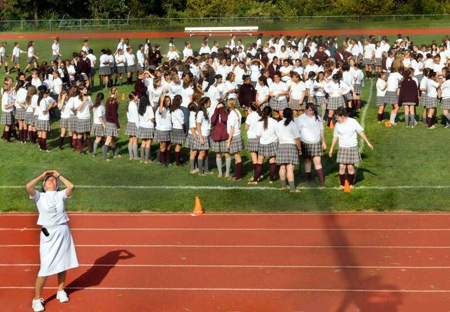 Sister Mary Jane Paolella looks for guidance from above as she tries to help Sacred Heart students get in formation for the Hamden school's 65th anniversary photograph.  A photographer in an overhead bucket directed the shot.  Melanie Stengel/Register