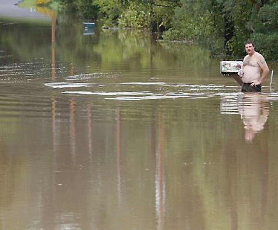 """Dispatch Staff Photo by JOHN HAEGER <a href=""""http://twitter.com/oneidaphoto"""">twitter.com/oneidaphoto</a> A man who declined do give his name stands in flood waters on Highland Avenue in the Town of Vernon on Thursday, Sept. 9, 2011. Residents of the area were evacuated  around 2:30 am as waters began to rise."""