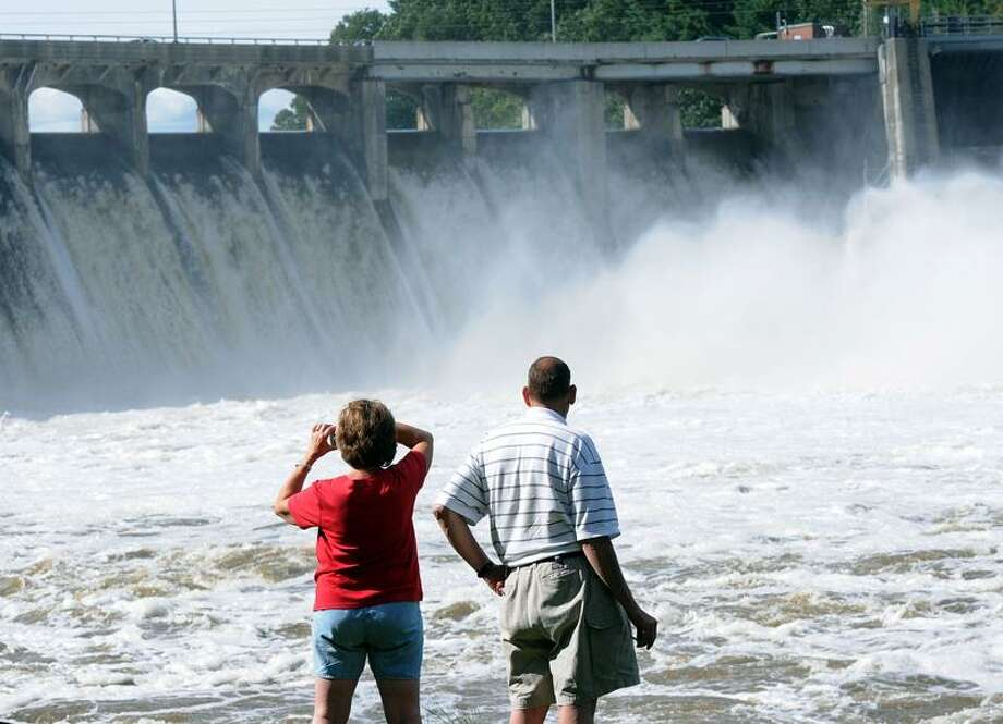Dan and Marie Piselli watch the raging waters over the Stevenson Dam in Oxford Thursday. Peter Casolino/Register