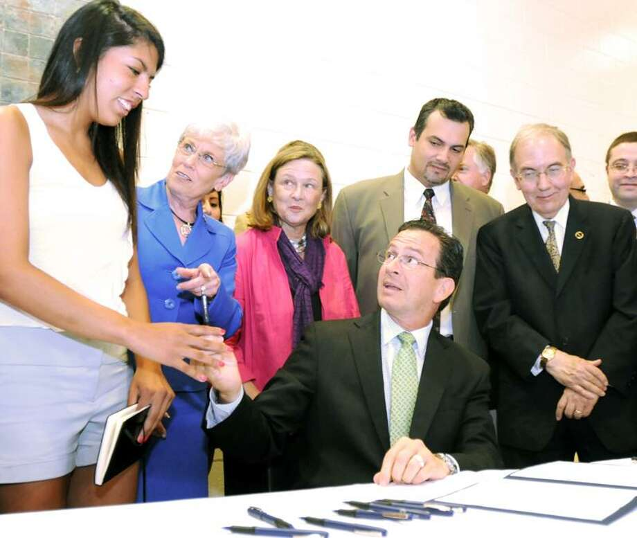 Gov. Dannel P. Malloy, seated center, gives the first pen to Maria Praeli, 18, a New Milford High School senior, during the ceremonial signing of an in-state tuition bill for illegal immigrants Thursday at Wilbur Cross High School in New Haven. Praeli is a native of Peru who came to the United States when she was 5. Also pictured are, from left, Lt. Gov. Nancy Wyman; state Rep. Patricia Dillon, D-New Haven; state Rep. Juan Candelaria, D-New Haven; and state Sen. Martin M. Looney, D-New Haven. Peter Hvizdak/Register