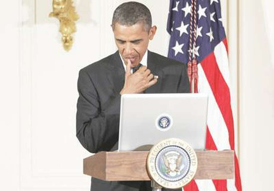 """President Barack Obama sends a tweet during a """"Twitter Town Hall"""" in the East Room of the White House in Washington, Wednesday, July 6, 2011. (AP Photo/Charles Dharapak) Photo: ASSOCIATED PRESS / AP2011"""