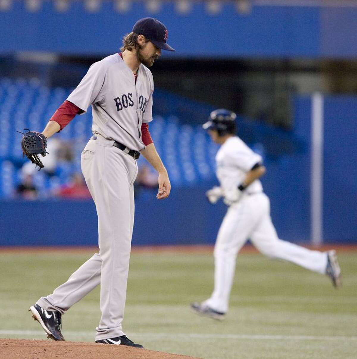 Boston Red Sox starting pitcher Andrew Miller, left, stands on the mound as Toronto Blue Jays' J.P. Arencibia rounds the bases following a three-run home run in the second inning MLB game baseball action in Toronto, Thursday, Sept. 8, 2011. (AP Photo/The Canadian Press, Darren Calabrese)