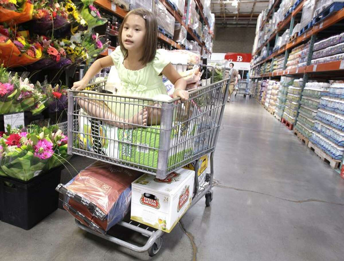 A girl sits in a shopping cart full of items at Costco in Mountain View, Calif. Shoppers go into Costco, TJ Maxx or a DSW shoe store looking for a bargain on something they need and end up splurging on irresistible finds.(Associated Press)
