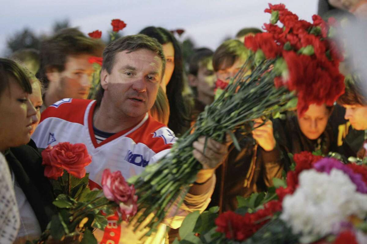 Fans of the Lokomotiv ice hockey team lay flowers and light candles at the Lokomotiv Arena to pay tribute to the Lokomotiv players killed in a plane crash, in the city of Yaroslavl, on the Volga River about 150 miles (240 kilometers) northeast of Moscow, Russia, Wednesday, Sept. 7, 2011. The Yak-42 jet carrying the Lokomotiv ice hockey team crashed while taking off Wednesday near Yaroslavl. It was one of the worst plane crashes ever involving a sports team. (AP Photo/Misha Japaridze)
