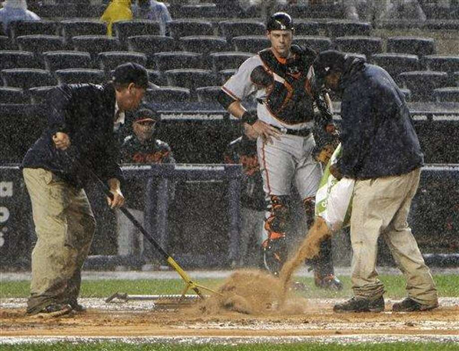 Baltimore Orioles catcher Matt Wieters waits for the grounds crew to dry the area around home plate during the fifth inning of a baseball game against the New York Yankees Tuesday, Sept. 6, 2011 at Yankee Stadium in New York. (AP Photo/Bill Kostroun) Photo: AP / FR51951 AP