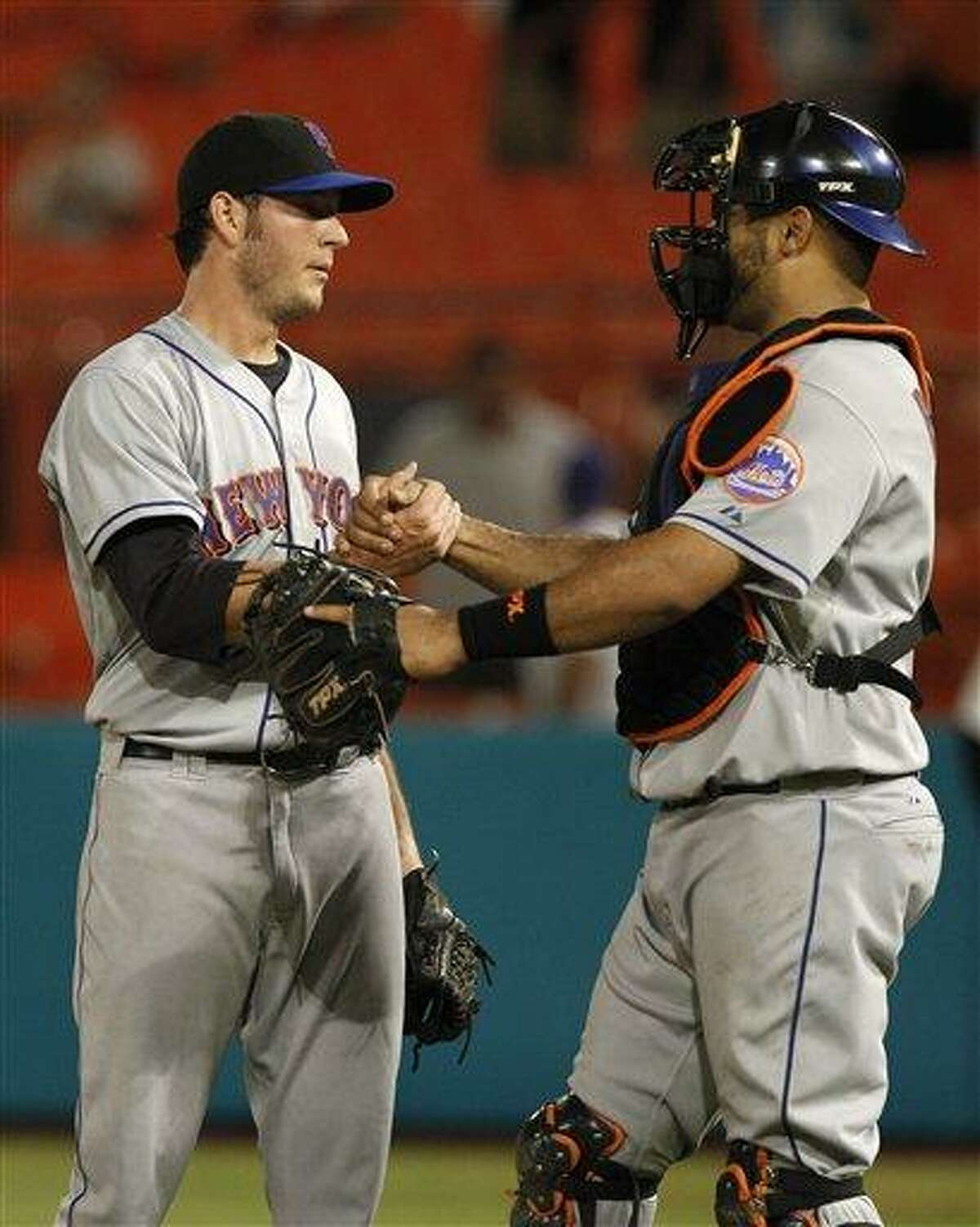 New York Mets relief pitcher Josh Stinson, left, shakes hands with catcher Ronny Paulino, right, after the Mets defeated the Florida Marlins 7-4 in twelve innings during a baseball game in Miami, Tuesday, Sept. 6, 2011. (AP Photo/Lynne Sladky)
