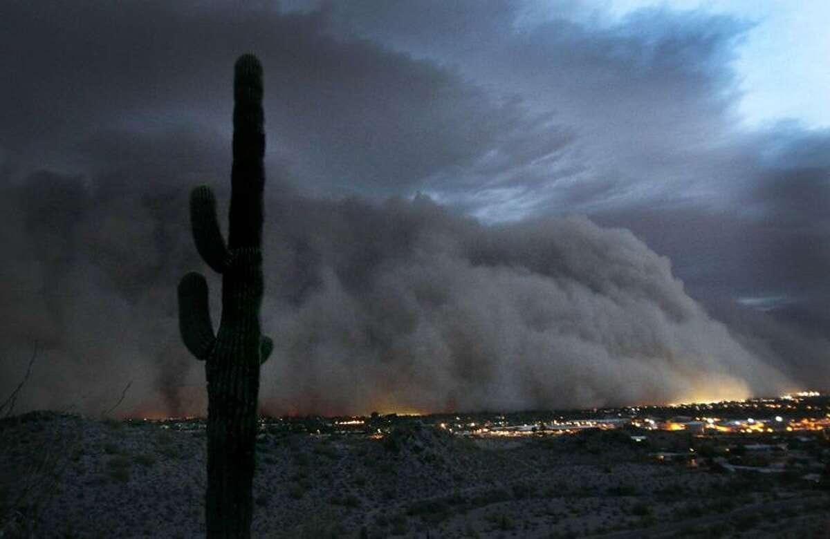 A giant dust storm engulfs Phoenix at about sundown Tuesday. Associated Press