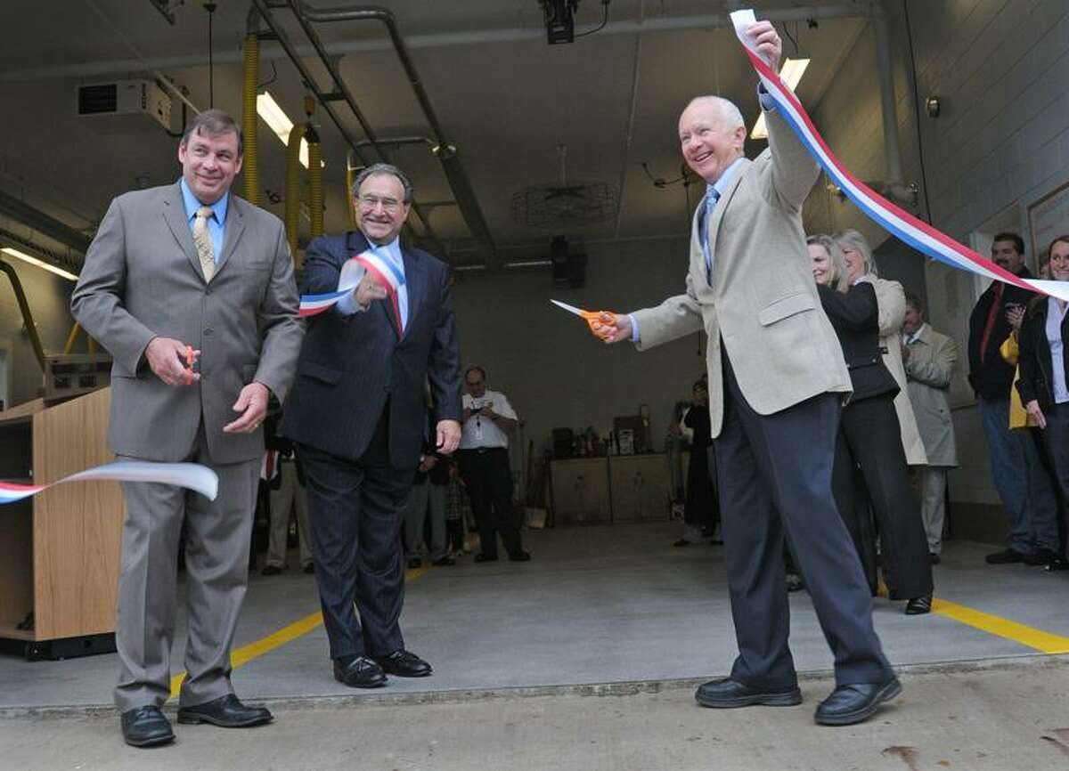 In this New Haven Register file photo, Fillmore McPherson, right, Madison first selectman, cuts a ribbon during a ceremony officially opening the Madison Ambulance Assn. headquarters on the corner of Route 79 and Old Route 79 in Madison. Peter Hvizdak/Register October 14, 2011 ph2385 Connecticut