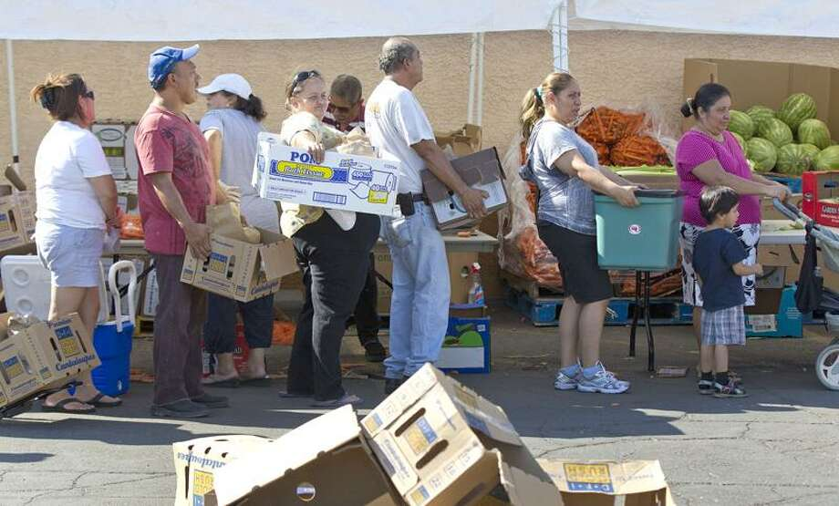 People stand in line waiting to fill boxes with food at the Living Faith Assembly Church food pantry Wednesday in Las Vegas. Associated Press