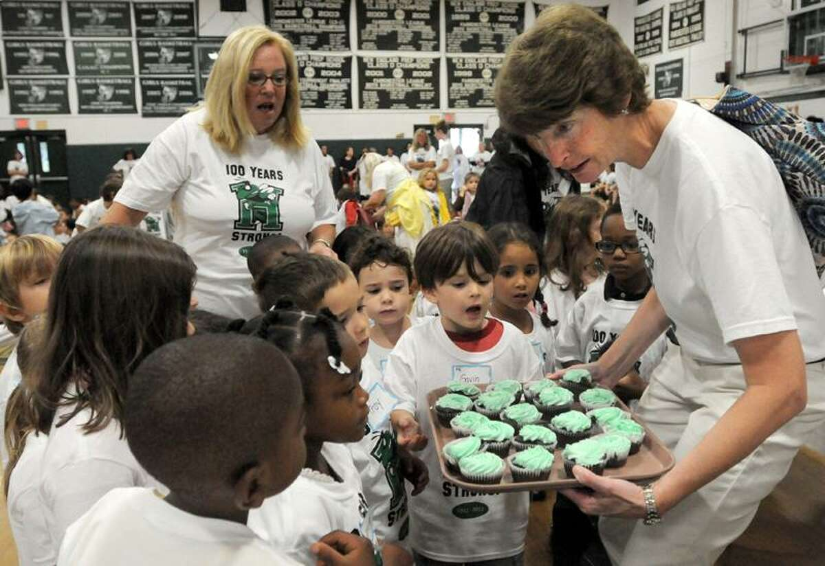 At an all-school assembly at Hamden Hall Country Day School in Hamden, pre-kindergarten teacher Claire Rich shows her students cupcakes they will eat later as the private school celebrates its 100th anniversary Tuesday. Peter Hvizdak/Register