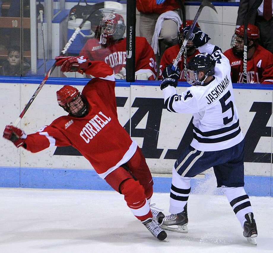New Haven-- Yale's Nick Jaskowiak puts the check on Cornell's Joel Lowry during the second period.  Peter Casolino/New Haven Register11/04/11