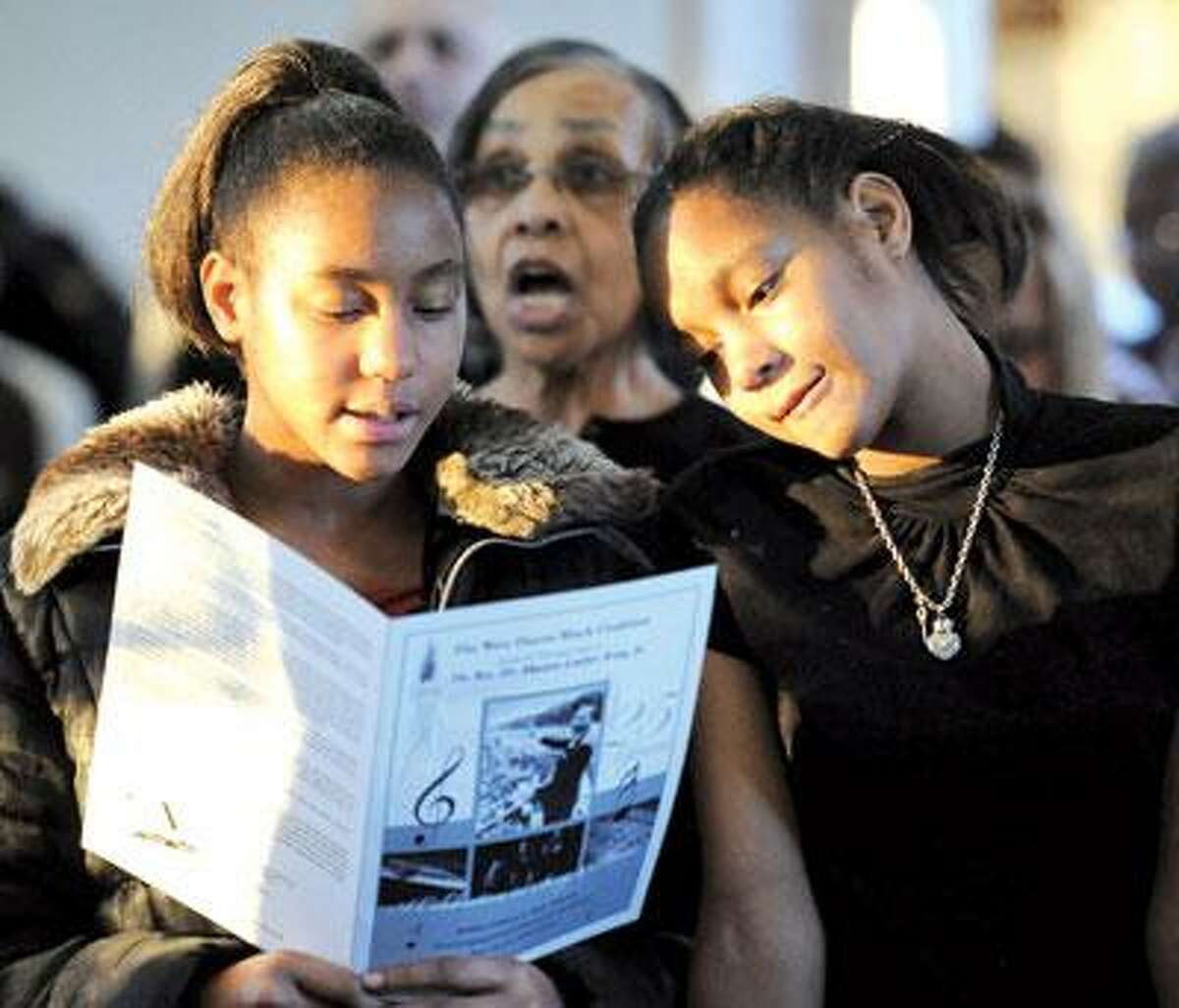 First Congregational Church, West Haven, was the site of the West Haven Black Coalition's 25th annual tribute to Martin Luther King Jr. Twin sisters Adrianne, left, and Alise Robertson, 11, of Hamden were among those in attendance. (Mara Lavitt/Register)