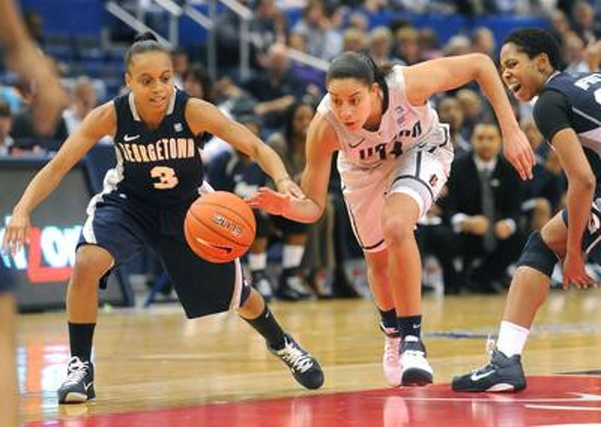 Hartford--UConn's Bria Hartley splits Georgetown defenders Rubylee Wright, left, and Monica McNutt during a Big East Tournament quarterfinal in Hartford Sunday. Photo by Brad Horrigan/New Haven Register-03.06.11.