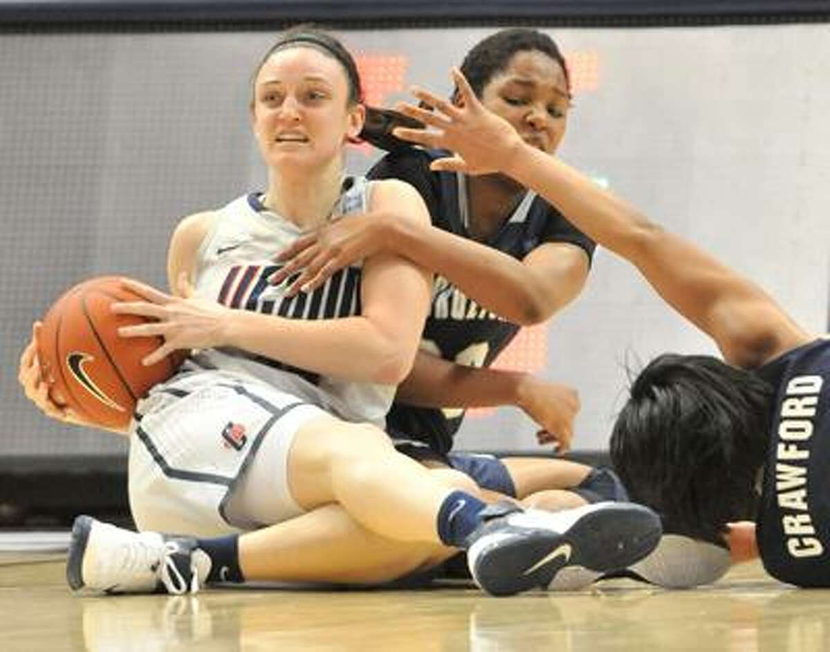 Hartford--UConn's Kelly Faris grabs a loose ball on the floor near Georgetown players Monica McNutt, center, and Adria Crawford during a Big East Tournament quarterfinal in Hartford Sunday. Photo by Brad Horrigan/New Haven Register-03.06.11.
