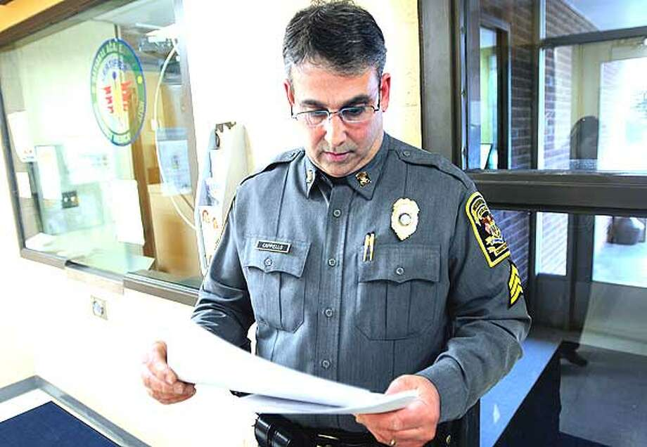 Woodbridge Sgt. Frank Cappiello reviews the report of Aaron Thomas' arrest on 9/3/2010 for fourth degree larceny at the Woodbridge Police Department. (Arnold Gold/Register)