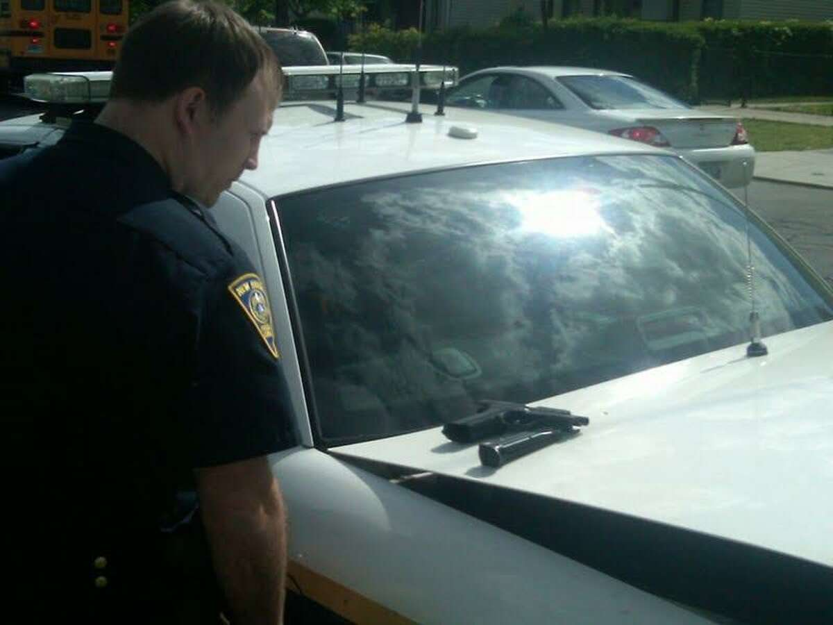 Officer Ryan Mcfarland examines a weapon seized in Newhallville, which ended up being a BB gun Photo by William Kaempffer