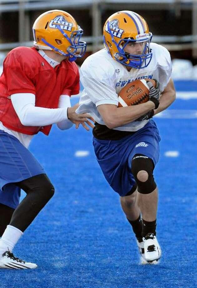 UNH football quarterback Ryan Osiecki left hands off to running back Michael DeCaro right during practice. Photo by Mara Lavitt/New Haven Register11/2/11
