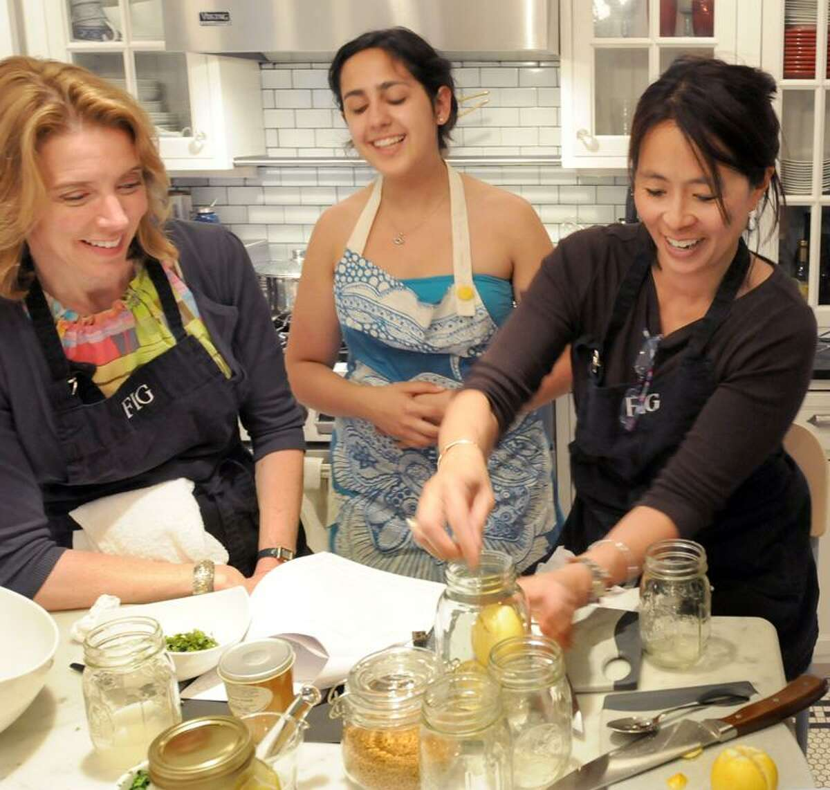 Students Eileen Bonetti of Farmington, left, and Kai Friedman try their hand at preserved lemons with school assistant Gabrielle Siegel, center, keeping an eye on things.