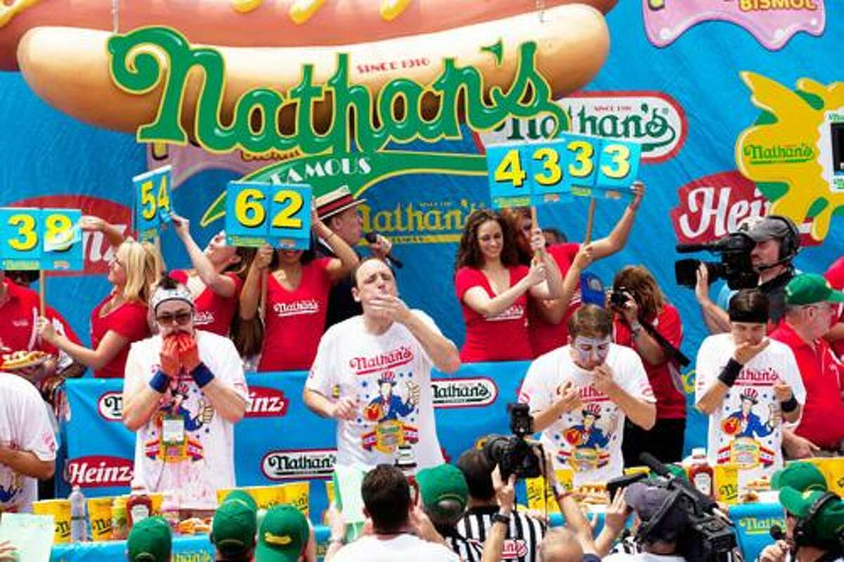 AP Photo by John Minchillo Four-time reigning champion Joey Chestnut, center, competes in his fifth Nathan's Famous Hot Dog Eating World Championship, Monday, July 4, 2011, in the Brooklyn borough of New York. Chestnut scarfed down 62 hot dogs to win his fifth consecutive Fourth of July hot dog eating contest at Coney Island -- the equivalent of about 20,000 calories in 10 minutes.
