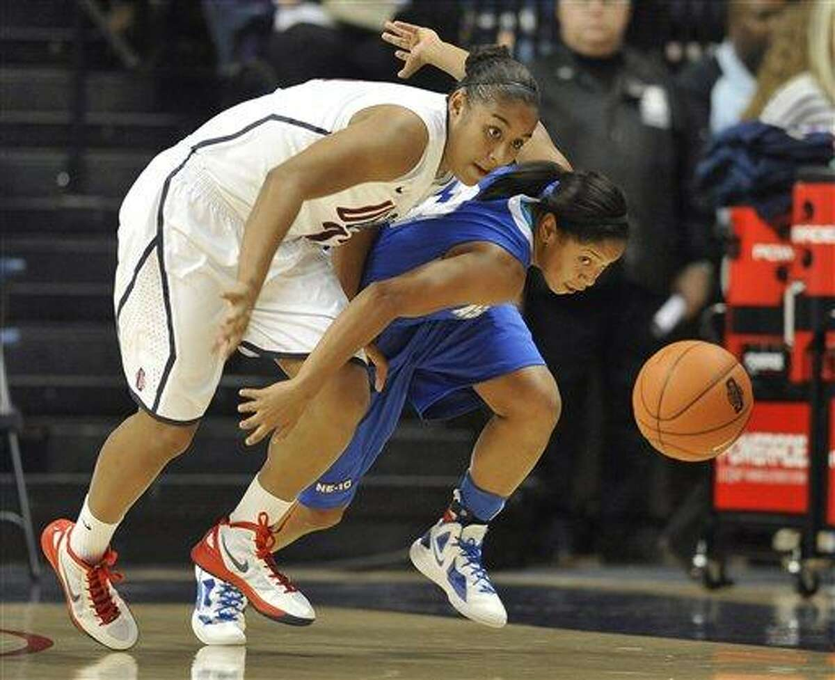 Connecticut's Kaleena Mosqueda-Lewis, left, and Assumption's Gabrielle Gibson, right, chase down a loose ball in the first half of an NCAA women's college basketball exhibition game Storrs, Conn., Thursday, Nov. 3, 2011. (AP Photo/Jessica Hill)