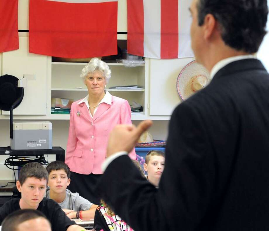 The new Milford Superintendent of Schools Elizabeth Feser watches West Shore Middle School Principal Vince Scarpetti welcome a class of eighth-graders at the start of the school day. Mara Lavitt/Register