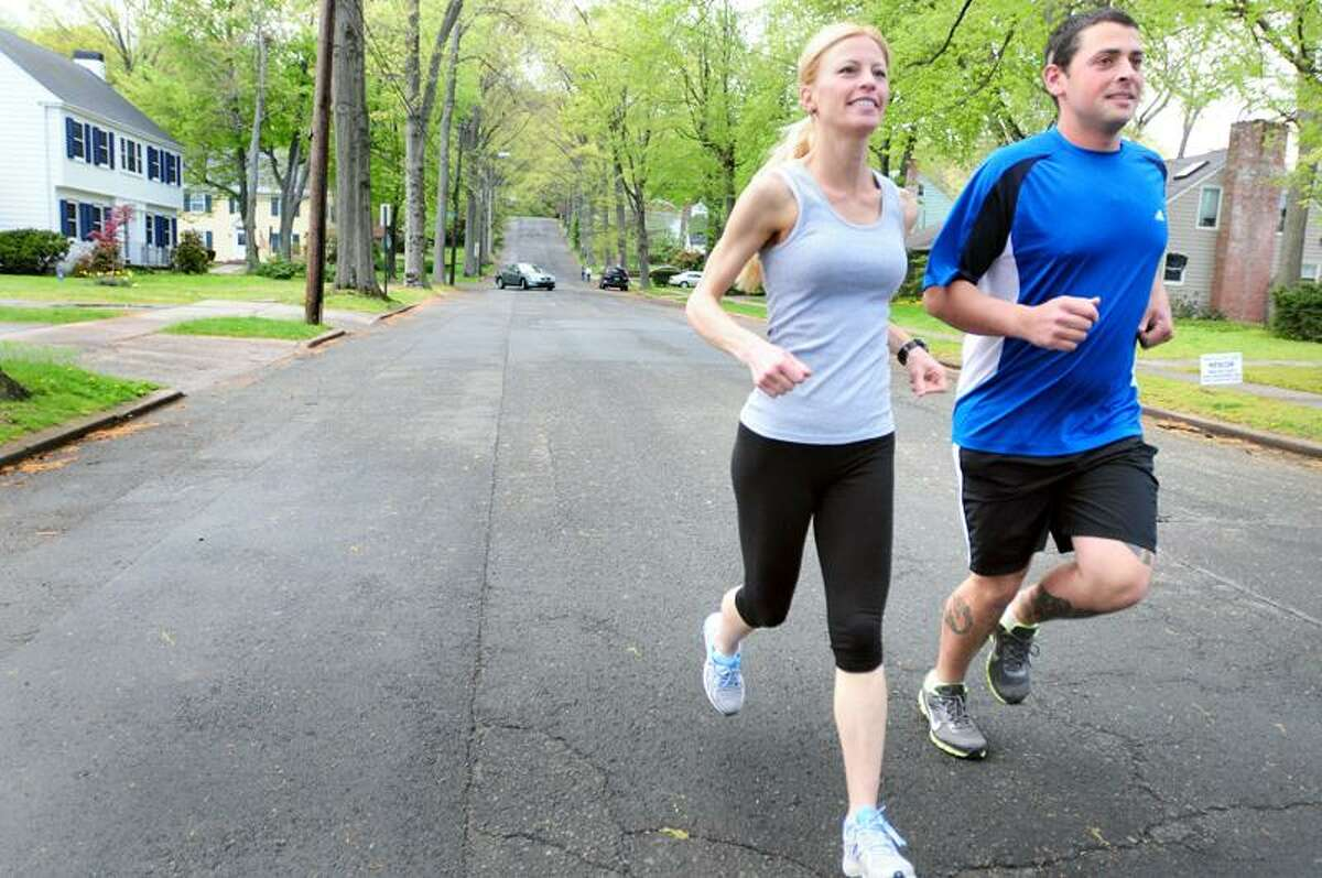 Ona Alpert and her husband, Todd Josselyn, run on Cleveland Rd. in New Haven Saturday, as they prepare for the 56-mile Comrades Marathon in South Africa on May 29. (Arnold Gold/Register)