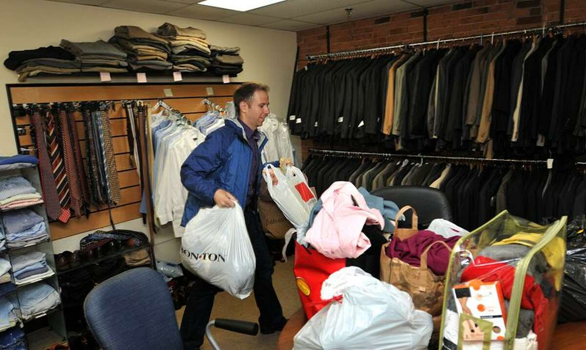 Anthem IT professional Noel Cyr brongs in bags of donated business clothes from Athem employees to the offices of STRIVE/New Haven. The profession business clothes are available to members of the STRIVE program and helps them dress for success at job interviews. (By Peter Casolino/New Haven Register)