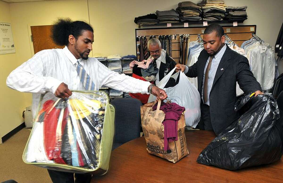 STRIVE/New Haven graduates TaeKwon Taylor, left and Jose Santiago, center, and Kendrick Baker, program manager, bring in clothes donated by Anthem employees to add to their collection. The profession business clothes are available to members of the STRIVE program and helps them dress for success at job interviews. (By Peter Casolino/New Haven Register)