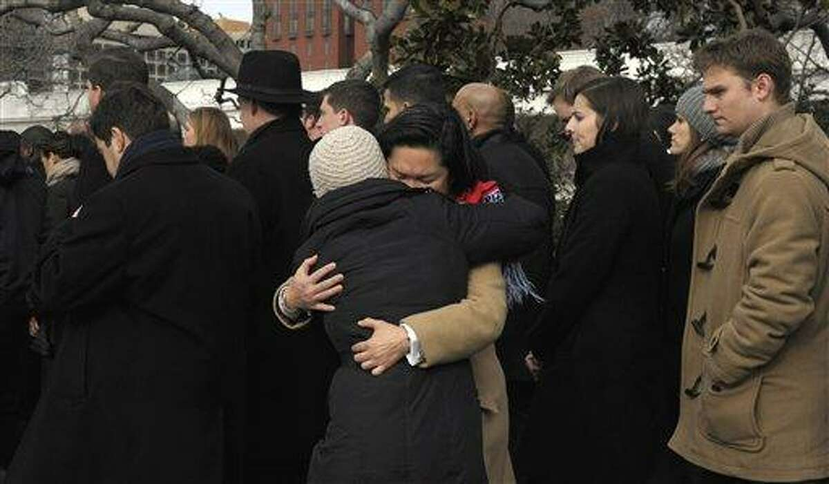 People hug as they walk from the South Lawn of the White House in Washington, Monday, Jan. 10, 2011, after observing a moment of silence with President Barack Obama, first lady Michelle Obama and other government employees to honor those who were killed and injured in the shooting in Tucson, Ariz. Rep. Gabrielle Giffords, D-Ariz., is in critical condition after being shot in the head. (AP Photo/Susan Walsh)