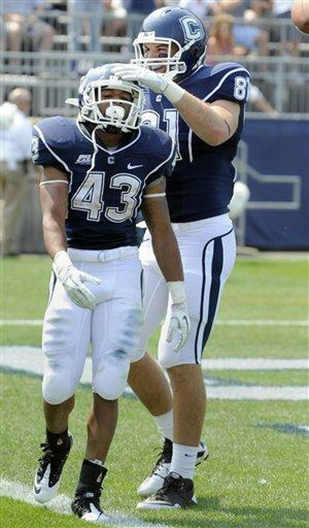 Connecticut's Lyle McCombs, left, celebrates with Corey Manning after scoring a touchdown during the first half of an NCAA college football game against Fordham in East Hartford, Conn., on Saturday, Sept. 3, 2011. (AP Photo/Fred Beckham)