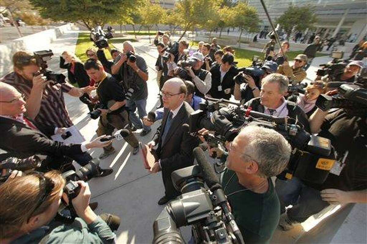 United States District Attorney Patrick Cunningham, center, talks to the press following the initial court appearance of Jared Loughner at the Sandra Day O'Connor United States Courthouse in Phoenix, Ariz., Monday, Jan. 10, 2011. Loughner appeared in federal court on charges he tried to assassinate Rep. Gabrielle Giffords in a shooting rampage that left six people dead. (AP Photo/Charlie Riedel)