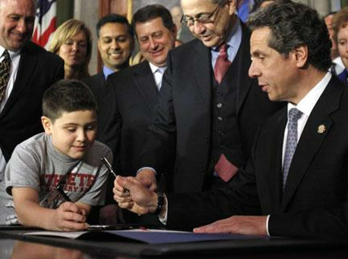 AP Photo New York Gov. Andrew Cuomo, right, hands a pen to Alexander Smith, 10, of Clifton Park after signing a bill mandating health insurers provide coverage for autism, at the Capitol in Albany on Tuesday. Smith is autistic.