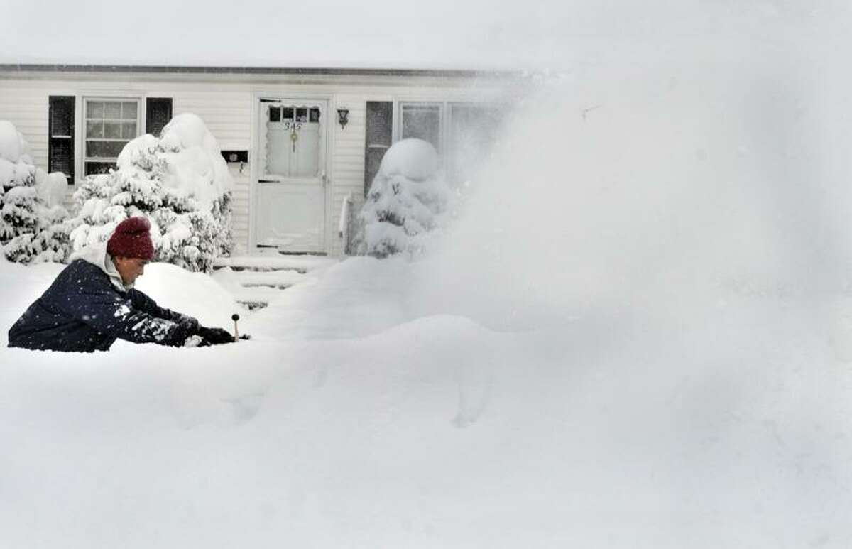 NEW HAVEN--Lee Jaafar cleans the snow fom a neighbor's house on Frederick street. He says that since he has a snowblower
